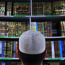 "A man wearing an Islamic prayer cap, or ""Kufi"", looks at Islamic books on display at a bookshop located in the western Sydney suburb of Lakemba October 3, 2014. Last month, the national security agency raised its four-tier threat level to ""high"" for the first time and about 900 police launched raids on homes in Sydney's predominantly Muslim western suburbs and in Brisbane. Only about half a million people out of Australia's 23.5 million are Muslims, making them a tiny fraction in a country where the final vestiges of the ""White Australia"" policy were only abolished in 1973, allowing large scale non-European migration. At least half of Australia's Muslims live in Sydney's western suburbs, which were transformed in the mid-1970s from white working-class enclaves into majority-Muslim outposts by a surge of immigration from Lebanon. Picture taken October 3, 2014. To match Insight MIDEAST-CRISIS/AUSTRALIA      REUTERS/David Gray      (AUSTRALIA - Tags: RELIGION POLITICS SOCIETY) - RTR491LT"